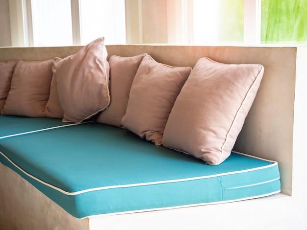 Molti cuscini beige su imbottiture verdi sul divano in cemento vicino alla finestra di vetro.