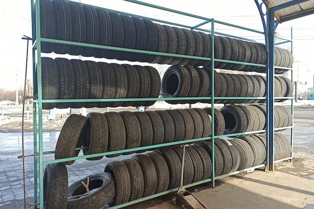 Molti pneumatici per auto in gomma nera sullo scaffale del negozio in vendita.