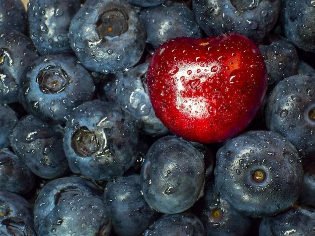 Tanti mirtilli e una ciliegia con tante gocce d'acqua. frutta fresca.