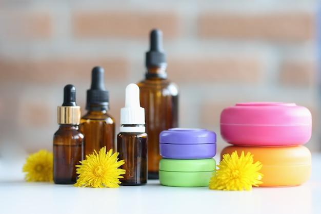 Molte bottiglie e barattoli con cosmetici sdraiato sul tavolo con il primo piano dei fiori gialli