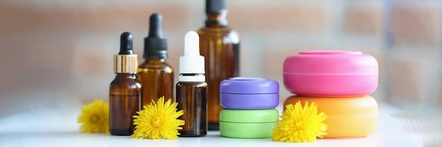 Molte bottiglie e barattoli con cosmetici sdraiati sul tavolo con fiori gialli in primo piano