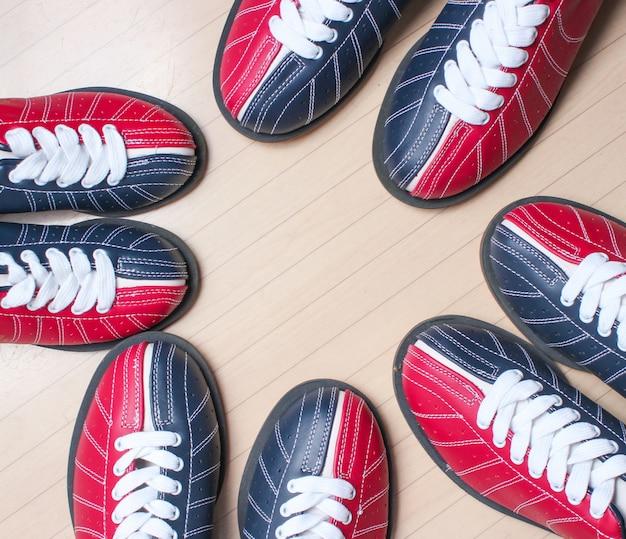 Molte scarpe da bowling sul pavimento.
