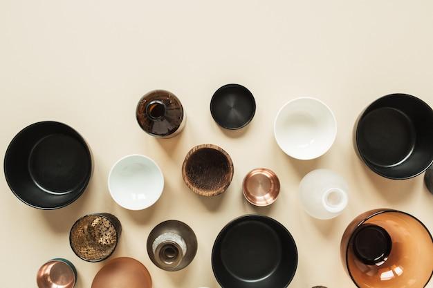 Molte ciotole, contenitori, piattini su beige pastello. vista piana, vista dall'alto di decorazioni in legno, ceramica e vetro.