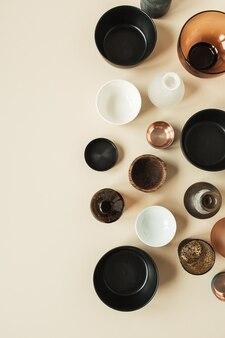 Molte ciotole, contenitori, piattini sulla superficie beige pastello