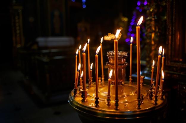 Molte candele accese stanno in un supporto dorato nella chiesa. messa a fuoco selettiva