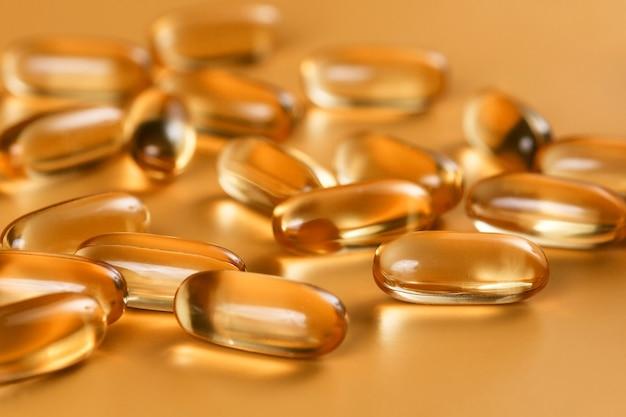 Molte capsule omega 3 su sfondo giallo. primo piano, prodotto ad alta risoluzione. concetto di assistenza sanitaria.