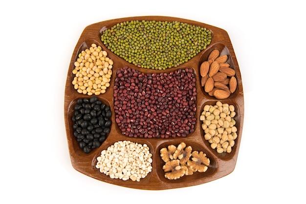 Molti cereali come noci, macadamia, piselli, mandorle e altri isolati su bianco.