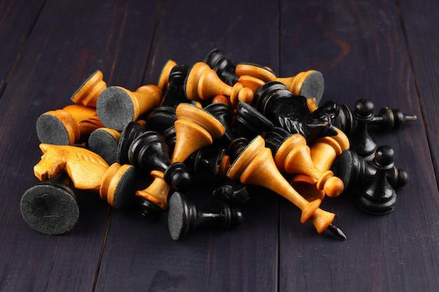 Molti pezzi degli scacchi su una superficie di legno scuro