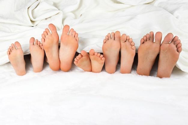 I piedi di molti bambini sbirciano da sotto le coperte
