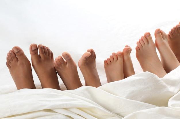 I piedi di molti bambini sbirciano da sotto la coperta