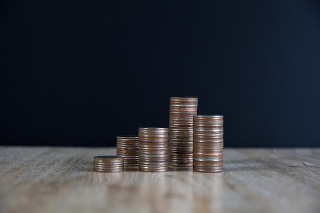Molte monete sono impilate in un grafico sul tavolo per idee di pianificazione finanziaria.