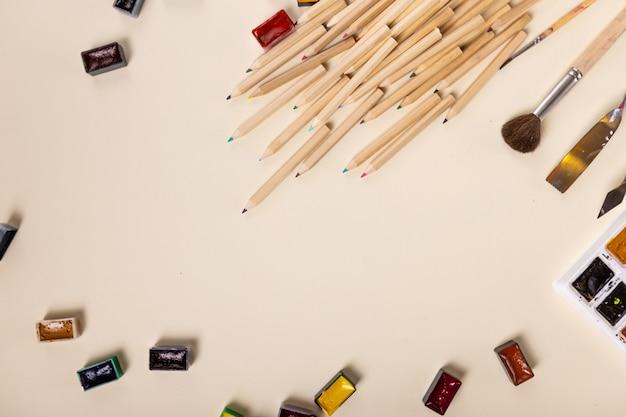 Molte matite colorate, colori e pennelli ad acquerello sono splendidamente disposti su uno sfondo chiaro...