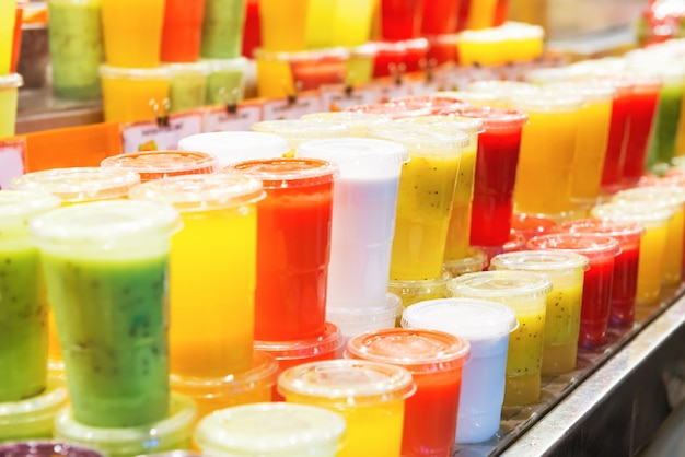 Molti bicchieri colorati con frullato di frappè di frutta in un mercato