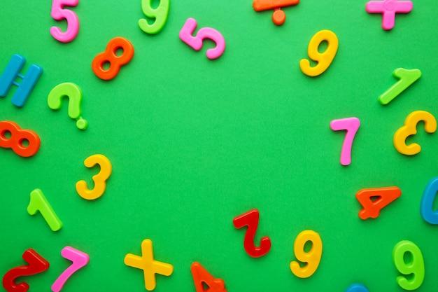 Molti numeri colorati su sfondo verde con spazio di copia. vista dall'alto