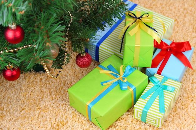 Molti regali colorati con nastri di lusso su sfondo di tappeti colorati