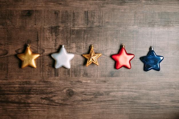 Molti colori di stelle metalliche come rosso, blu, oro e argento su fondo in legno.
