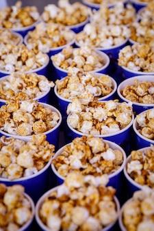 Molte tazze di popcorn prima del film. vista laterale, messa a fuoco selettiva