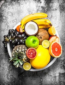 Molti frutti diversi in una grande ciotola. su fondo rustico.