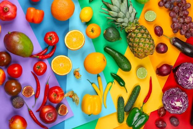 Molti diversi tipi di frutta e verdura su sfondo arcobaleno