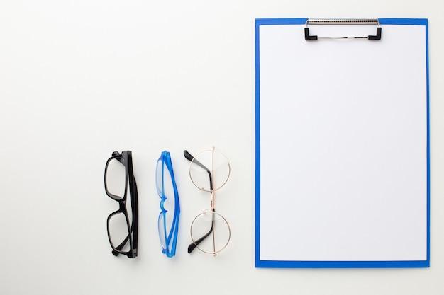 Molti occhiali diversi per la visione si trovano sul desktop vicino alla cartella per il testo.