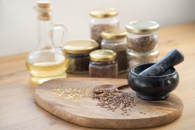Molte diverse erbe medicinali in cucchiai di legno su uno sfondo di legno scuro. pillole omeopatiche.