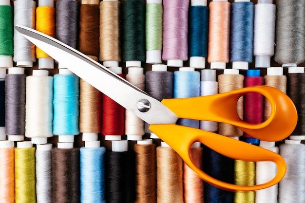 Molte bobine diverse con fili, disposizione piatta, vista dall'alto. filo colorato e forbici da sarto, primo piano