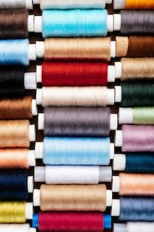 Molte bobine diverse con fili, disposizione piatta, vista dall'alto. fili colorati, primo piano, sfondo luminoso.