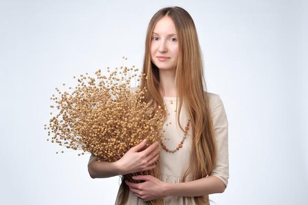 Molti fiori secchi di lino nelle mani di una bella ragazza con i capelli lunghi.