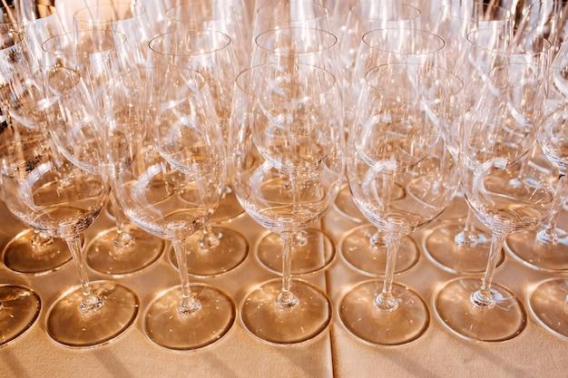 Molti bicchieri di champagne vuoti si chiudono. calici di vetro sul tavolo bianco. bicchiere da vino in cristallo vuoto. calice di vetro su una gamba alta.
