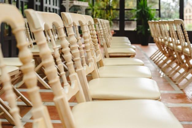 Molte sedie di legno bianche vuote allineate per un evento in stile retrò.