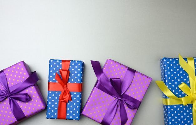 Molte scatole regalo legate con un nastro di seta su uno sfondo grigio, vista dall'alto. sfondo festivo, copia spazio