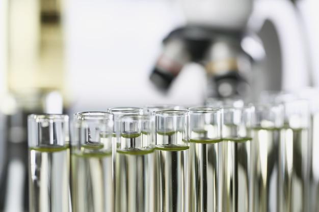 Molte provette di vetro con liquido giallo in piedi in primo piano del laboratorio