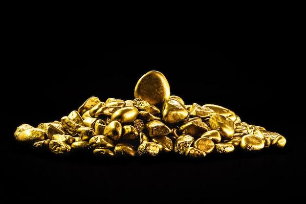 Molte pepite d'oro su sfondo nero isolato, concetto di ricchezza e minerali rari