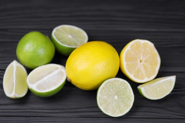 Molte metà e fette di limone giallo e calce verde sulla tavola di legno nera. frutta fresca in cucina con copia spazio per il testo