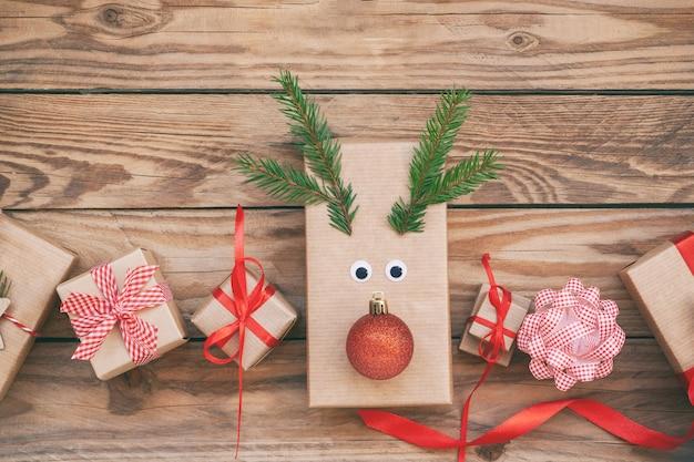 Molte scatole regalo di natale a zero rifiuti fatte a mano su fondo di legno. sfondo di natale con decorazioni natalizie. disposizione piatta.