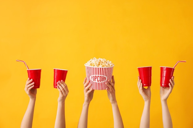 Molte mani con popcorn e tazze di bevanda sul colore