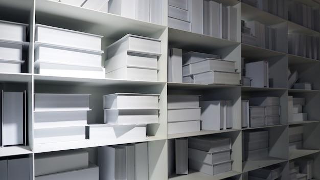 Molti libri di colore bianco con copertina rigida sullo scaffale in acciaio utilizzato per il design della decorazione d'interni.