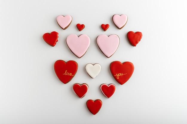 Molti biscotti a forma di cuore con glassa di zucchero di colore. sfondo bianco, vista dall'alto. san valentino trattare.