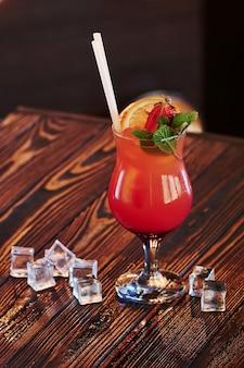 Molti cubetti di ghiaccio sono sul tavolo. il cocktail è pronto.