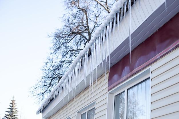 Molti ghiaccioli di diverse lunghezze appesi sul tetto dell'edificio. vista laterale