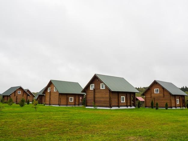 Molte grandi case di tronchi identiche all'esterno con un cortile coperto d'erba