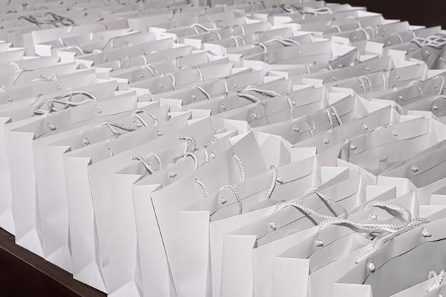 Molti sacchetti regalo identici di cartone bianco su uno sfondo scuro