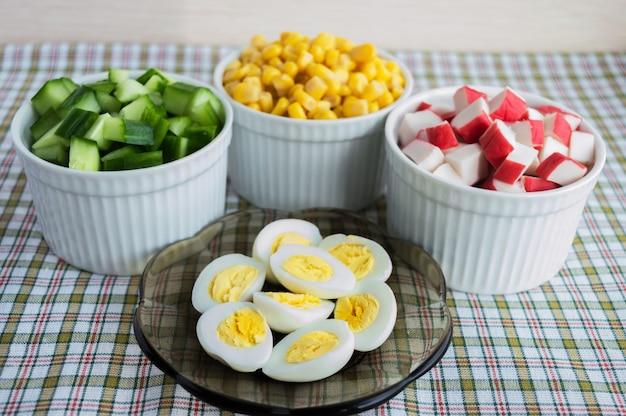 Molti ingredienti per l'insalata (mais dolce, cetriolo, polpa di granchio, uova di quaglia) su sfondo chiaro.
