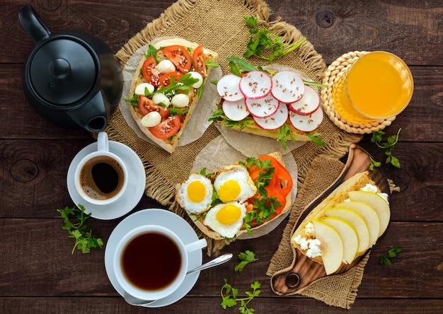 Molti tipi di panini, bruschette e tè, caffè, succo fresco, colazione in famiglia la vista dall'alto?