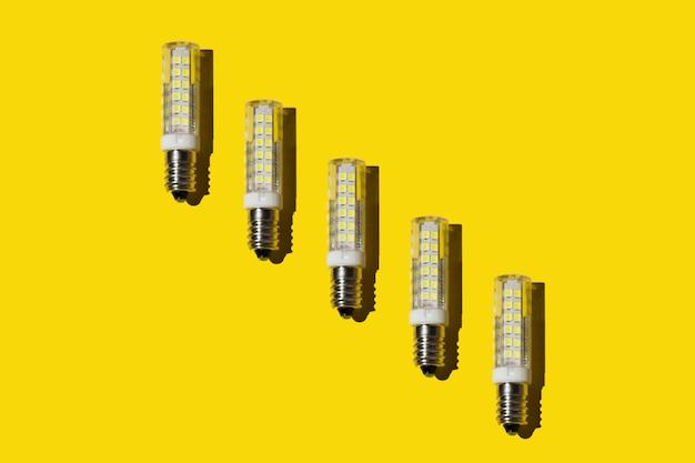 Molte lampadine moderne a risparmio energetico su sfondo giallo