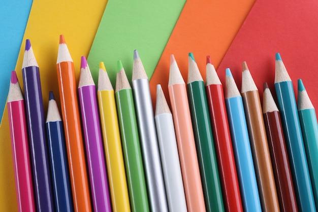 Molte matite multicolori che giacciono su colori brillanti