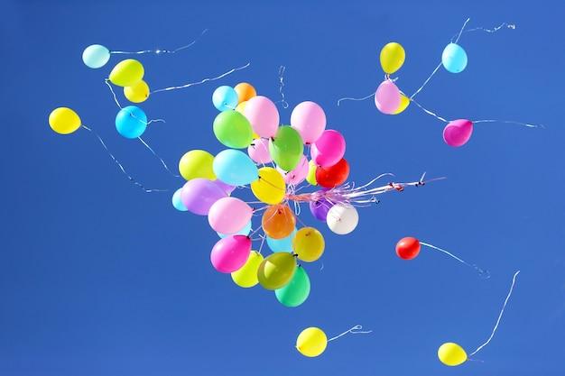 Molti palloncini multicolori che volano nel cielo blu. articoli per celebrare eventi