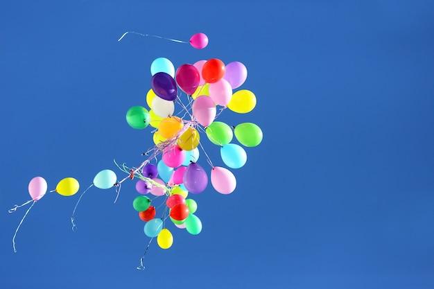 Molti palloncini multicolori che volano nel cielo blu