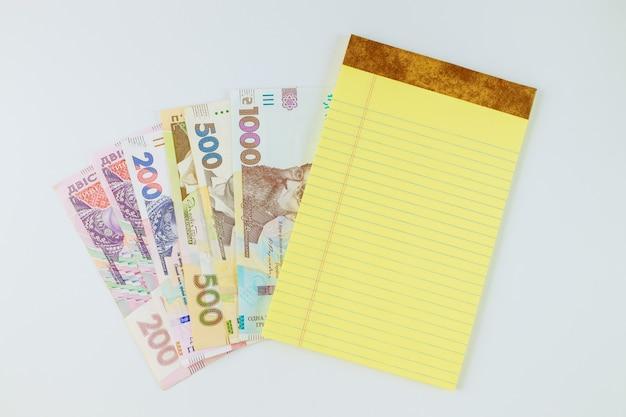 Molte nuove banconote grivna ucraina nel taccuino giallo su sfondo bianco