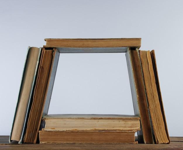 Molti vecchi libri, tubo di fumo sulla mensola in legno contro il muro bianco